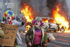 Los manifestantes disfrazados de payasos pasan cerca de un carro en llamas en Fráncfort, Alemania. Los activistas buscan bloquear la nueva sede del Banco Central Europeo en protesta por la austeridad del Gobierno y el capitalismo. (AP)