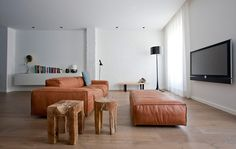 Interior by Studio Montañana - look at the gorgeous pinched edges and caramel colour of that sofa and footstool!