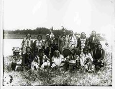 "File Hills, Saskatchewan, 1914 Entitled: ""Old Generation, File Hills Indian Agency"". The Image includes (back row, from left) Mrs. Keewaydin, Mrs. Jack Fisher, Mrs. Miss-ta-tik, Mrs. Buffalo Bow, Day Walker, Mrs. Yellow Belly, Mrs. Pimotatt, and Mrs. Playful Child (Tuckanow); (front row) Chief Hawke, Crooked Nose, Chief Star Blanket, Pointed Cap (Cheepoostatin), Buffalo Bow, Miss-ta-tik, and Kuinness (Cree)."