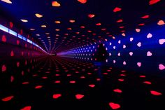 """Studio Vollaerszwart conceived this """"Tunnel of Love"""", luminous experience made within the Festival Glow in Eindhoven. Using thousands of paper hearts, the tunnel offers a warm light and a place to focus on the interaction between architecture and the feeling of joy that the installation can cause."""