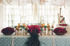 Head table with low full centerpieces, candles, succulents and peacock feathers