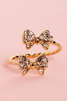 Check it out from Lulus.com! Give yourself the gift of dazzling digits with the Bowfinger Gold Rhinestone Bow Ring! A twisted metal band opens up in front to show off two pretty, rhinestone-covered bows. Bows measure just under 1/2