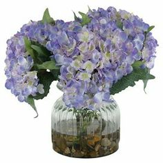 """Faux hydrangea arrangement in a glass vase. Made in the USA.  $53 Product: Faux floral arrangementConstruction Material: Silk and glassColor: LavenderFeatures:  Includes faux hydrangeasMade in the USA Dimensions: 13.5"""" H x 15"""" Diameter"""