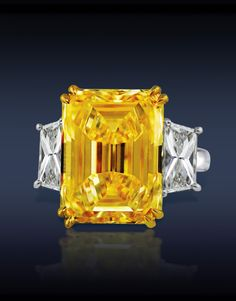 Fancy Intense Yellow Diamond Solitaire, Featuring: GIA Certified 20.18 Ct VS1 Emerald Cut Diamond, Surrounded by 2.72 Ct G VS1 Trapezoid Diamonds (2 Side Stones), Mounted in Platinum.