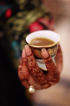 This image is mesmerizing. I love the glint of the pearl on the henna'd hand.