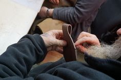 Ross starts to hand stitch one of the leather sheaths under Mark's guidance.