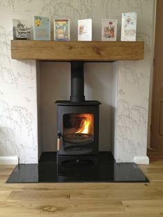 Charnwood C-FOUR on polished granite hearth with oak fireplace beam and painted recess.