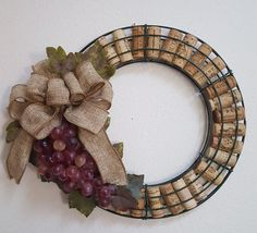 Great wreath for the wine-lover in your family! The wreath frame is filled with assorted wine corks, and decorated with silk grapevine leaves, a purple grape bunch, and bow. This wreath would look great on a door or hanging in a kitchen or bar area! The width of the wreath is approximately 12.