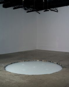 water drips from 5 rods suspended from the ceiling, falling into a concrete crater dug out of the gallery floor. the flow of water is manipulated to create specific sounds in regular patterns and intervals lending to the symphonic structure of the artwork. the liquid appears milky white and the pool has an eerie glow