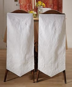 """Mr. & Mrs. Wedding Chair Banner Set made of crisp, white linen. Th top of the banners are embroidered in white with """"Mr."""" on one and """"Mrs."""" on the other. The bottom of each banner features floral embroidery complete with leaf and vine details. This floral embroidery also has scattered crystals."""