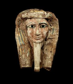An Egyptian polychrome painted wood sarcophagus mask  Third Intermediate - Late Period, circa 1000-600 B.C. Wearing a long false beard and a yellow and turquoise striped tripartite wig decorated with the remains of a scarab at the top, the serene pink face with inlaid bronze eyebrows, one now missing, and bronze and white stone eyes, the pupils painted in black, 48cm high  BONHAMS 4/16/2015