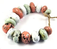 Seeds of a singularity --  16 dark, rustic stoneware beads with holes in pastel colours from HappyFallout on Etsy.