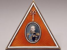 Dowager Empress Maria Fedorovna purchased this frame from Fabergé in 1896, after the death of her husband, Alexander III. It was presumably a gift to someone who wanted his portrait for a keepsake. The triangular frame is decorated in red enamel in a sunburst pattern emanating from the miniature, as if Alexander should be seen in a blaze of glory. The bow at the apex illustrates Fabergé's quintessential neoclassical style.