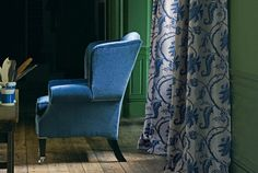 Room with green paneled walls and blue and white curtains (Winterthur Leaf fabric by Zoffany)