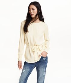 Check this out! Long-sleeved blouse in woven crêpe fabric with lace trim at shoulders and cuffs. Opening at back of neck with button, tie belt at waist, and rounded hem. - Visit hm.com to see more.