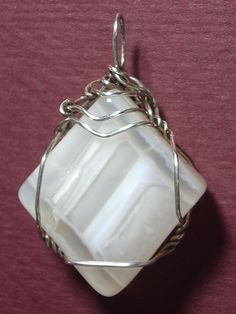 This interesting stone provides diagonal banding of clear and white opal and/or chalcedony. Wears well with many colors; better with gray toned versus brown toned colors. It generally wears well with