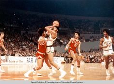 Color photo of University of Oregon basketball players Greg Ballard (with the ball) and Ronnie Lee (on the perimeter) in a game against Washington State on December 30, 1974 during the Far West Classic at Memorial Coliseum in Portland. The Ducks won the game 74-65. ©University of Oregon Libraries - Special Collections and University Archives
