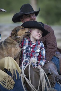 Talk about contentment - leaning against Daddy, big old cowboy hat on with chaps and your best friend loving on you.