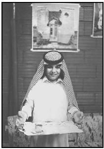 A young man presents coffee on a tray to a guest. The Saudis take pride in their hospitality, and it is considered rude to refuse.