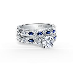 This nature-inspired design with floral details is from the Dahlia collection. It features 1/8 ctw of diamonds and 1/5 ctw of blue sapphires. The signature handcrafted details include floral hand engravings, peek-a-boo diamonds and milgrain edging. The center 1 carat round stone (shown) is a customized option.