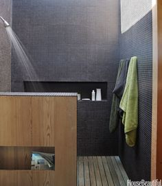 In the master-bath shower of a modern New York beach house designed by architect Cary Tamarkin, the walls are clad in black porcelain tiles that soar up to a wall-to-wall skylight. See more beautiful bathrooms.