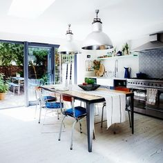Modern Victorian home renovation in London, oversize industrial lighting, skylight, dark blue kitchen