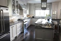 A three tier island, glass door upper cabinets, wood floors, & just the right accessories this kitchen is really lovely.