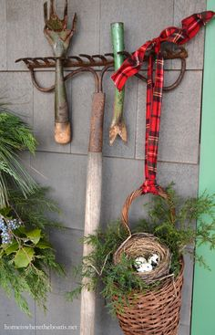 Christmas around the Potting Shed, Old rake with some vintage gardentools and a basket tied with tartan ribbon, filled with additional cedar and a bird nest.