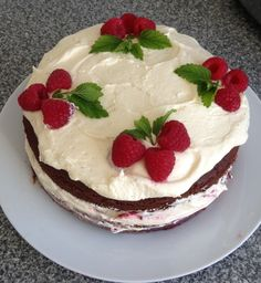 Chocolate cake (the 'I don't give a damn' one from Lorraine Pascale's book) sandwiched with vanilla butter icing and raspberry jam. The top is decorated with the same icing, fresh raspberries and mint sprigs.