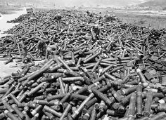 GIs and Korean service corpsmen stack up the enormous pile of empty artillery and mortar shell casings at a collecting point near the front, pointing to the huge amount of lead thrown at the enemy in four days of fighting for outpost Harry, June 18, 1953. (AP Photo/Gene Smith) #