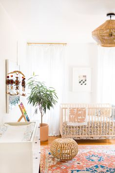 beautiful cali modern boho nursery. Love the rattan the vintage rug and those warm terra cotta colors