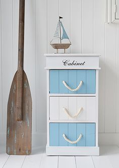 A great fixture for nautical bathrooms, this cabinet features a classic blue and white scheme with rope handles.