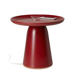 Functional furniture design at its best! A contemporary red side table with a pedestal base with added utility: a channel for cable management. An elegant solution for charging a phone or plugging in a lamp. On side table by Italian designer Luca Nichetto for Zaozuo.