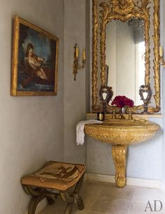 A powder room featuring a a Louis XV mirror set and a Siena marble sink with 1940s bronze fittings | archdigest.com