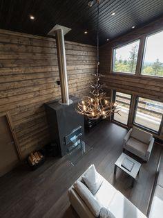 The living room of this gorgeous log cottage reaches its full beauty and potential with the help of Winled's Iiris -LED lights. Upean hirsimökin olohuone korkeine kattoineen pääsee täyteen loistoonsa Winledin Iiris -valaisinten avulla.