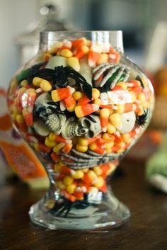 Una idea divertida poner arañas y esqueletos en jarrones de frascos con dulces para halloween. #DecoracionHalloween