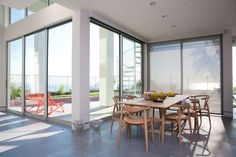 Dining area of modern California Home in San Clemente designed by Peggy Dupuis. The home features retractable, mobile plate glass.