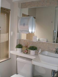 Aproveitamento total da pequena área de parede. Espelho com porta papel, bancada estendida acima caixa acoplada, cuba sobrepor.