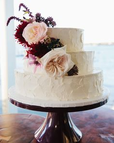 This textured three-tiered almond cake from Mayflour Confections was covered with almond-buttercream frosting and fresh flowers,filled with raspberry preserves, and served with raspberry coulis.