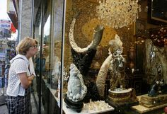 Picture of woman looking at ivory products for sale in shop window