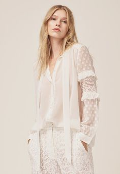 Lightweight crepe, frills and subtle polka dots combine to create the utterly romantic Comino Patched Blouse. The long-sleeved white blouse has a delicate feel and a form-skimming draped shape, with a relaxed bow neck tie. The sleeves are finished with ruched material and frills at the elbow, and a sheer polka dot pattern creating a pretty detail. Wear with white lace trousers for an impactful and modern take on bridal wear. Read more at…