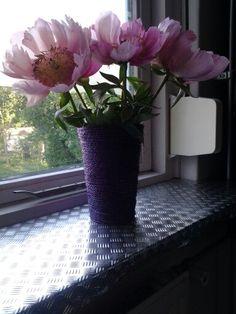 Een vaas omwikkelt met touw en die paars gespoten met spuitbusverf.