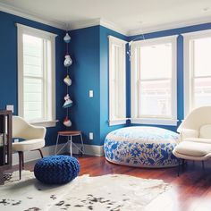 Teal Painted Walls, Bright White Window Frames & Crown Molding, Blue & White Patterned & Textured Poufs, Lots of Natural Light // via sonyayu
