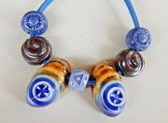 Mix beads amber and blue. The set consists of 7 ceramic beads , hand carved . By Mª Carmen Rodriguez ( Majoyoal ) https://www.facebook.com/groups/CeramicArtBeadMarket