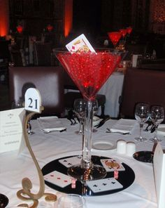 A Giant Martini Glass Filled With Red Balls And A Card Sticking Out   On A  Black Base.