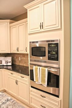 Fabuwood Cabinetry, Wellington Ivory finish & Wellington Spice, two tone kitchen cabinets, two tone granite, tumbled stone backsplash in ivory and espresso. Double Wall Oven Cabinet; keeping things elevated off the ground and simple!