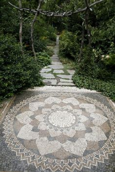 Beautiful fancy mosaic garden path in the backyard that has fountain/pond at the end