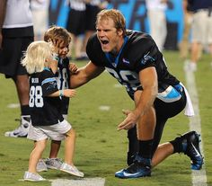Carolina Panthers tight end Greg Olsen, right, greets son Tate, left, and daughter Talbot following Fan Fest at Bank of America Stadium on Friday, August 7, 2015.