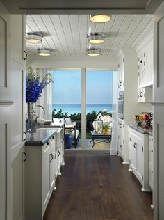 Coastal kitchen. Nice floor color/ cabinet color contract/ ceiling T&G, cabinets all the way to the ceiling.