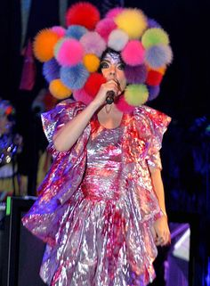 Bjork arrives onstage at London's Hammersmith Apollo wearing a pink and gold iridescent ballgown made entirely of ruffles, topped off by a fluffy head-dress of multicoloured pom poms